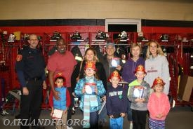 Assistant Chief Dave Hutsebaut with the families that won new alarms