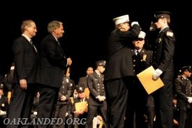 Assistant Chief Vincent Dies salutes his newest Firefighter Ethan LeRoy