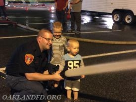 Fireman Tim DeBlock shows his son how to use the fire hose