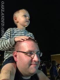 A son watching intently while sitting on dad's shoulders