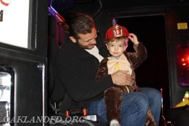 A future Oakland fireman enjoys sitting with Dad in the fire truck