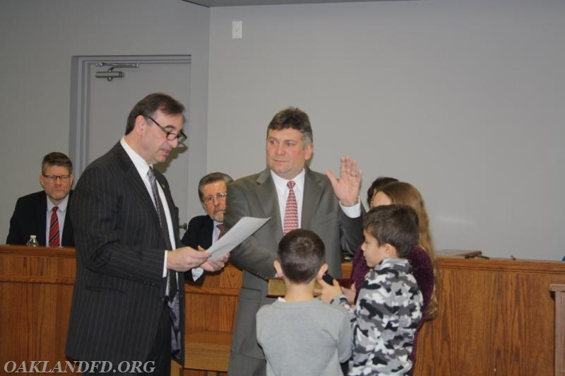 Councilman Russell Talamini takes his Oath of Office from John McCann while his children hold the Bible