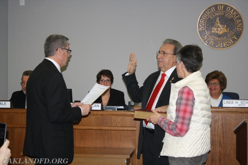 Councilman Pat Pignatelli takes his Oath of Office from Borough Attorney Brian Chewcaski while Pat's wife holds the Bible