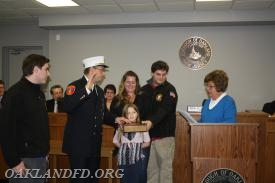 Department Chief Vincent Dies takes his Oath of Office from Mayor Linda Schwager as his family looks on