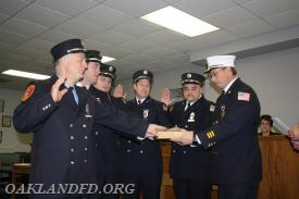 Captain Vincent Incorvaia, Lieutenants Don Johnston, Matt Sorce, Steven Longa and Engineer Leigh Dodd get help from Chief Dies for their Oath of Office