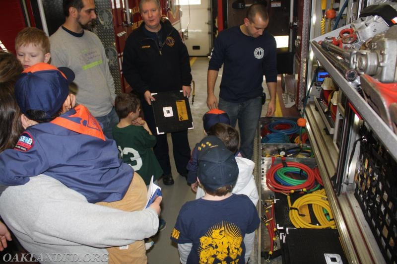 Firefighter Mike Curran talks about equipment with Troop leaders and parents while the Tiger Cub listen