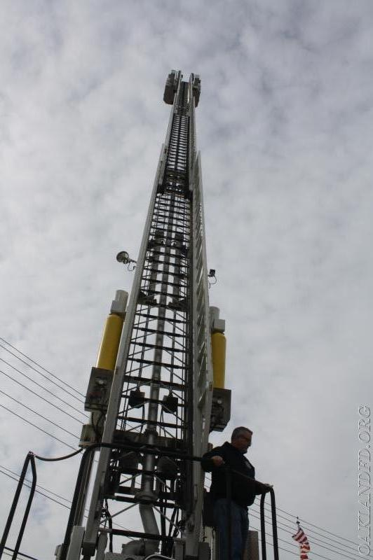 Firefighter Robert Knapp demonstrates the height of the ladder truck when extended
