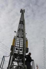 Firefighter Robert Knapp demonstrates the height of the ladder truck when extended
