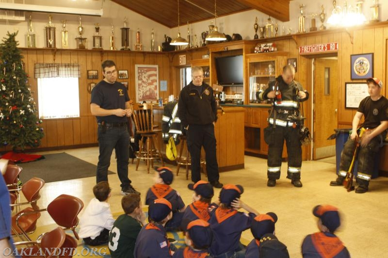 Firefighter Jeff Binder shows the Tigers his Turnout Gear while Jr. Firefighter Riley Beach and Firefighter Mike Curran look on