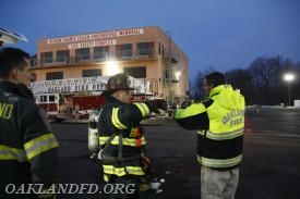 Chief Dies and Captain Incorvaia review assessing a building upon arriving at the scene